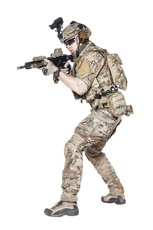 Member of US Army rangers in combat uniforms with his shirt sleeves rolled up, in helmet, eyewear and night vision goggles, ready to firing. Low readiness position. Studio shot, white background