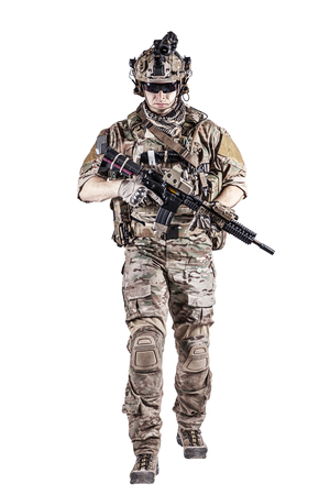 his shirt sleeves: US Army rangers in combat uniforms with his shirt sleeves rolled up, in helmet, eyewear and night vision goggles moving walking towards camera. Studio shot, white background