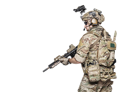 his shirt sleeves: Elite member of US Army rangers in combat uniforms with his shirt sleeves rolled up, in helmet, eyewear and night vision goggles. Studio shot, white background