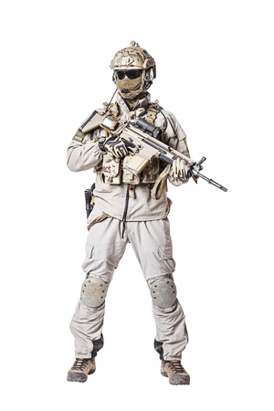 mag: Army soldier in Protective Combat Uniform holding Special Operations Forces Combat Assault Rifle. Knee pads, mag recovery pouch, chest rig, military boots. Studio shot, isolated on white background Stock Photo
