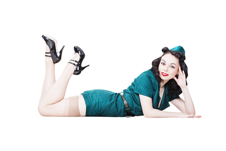 Portrait of Beautiful Brunette with black hair. Pin up Female Dressed in military clothing Uniform and Garrison cap feet up. Army Pin-up Girl Concept Stock Photo