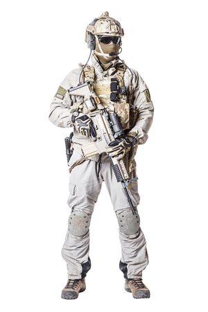 mag: Army soldier in Protective Combat Uniform holding Special Operations Forces Combat Assault Rifle. Knee pads, mag recovery pouch, chest rig, military boots. Studio shot, isolated on white Stock Photo