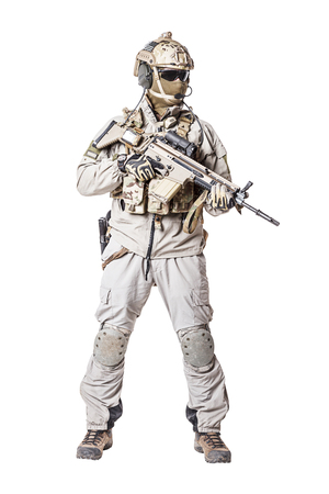 Army soldier in Protective Combat Uniform holding Special Operations Forces Combat Assault Rifle. Knee pads, mag recovery pouch, chest rig, military boots. Studio shot, isolated on white background Stock Photo