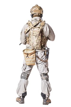 특수 작전 부대를 보유한 방어 전투 유니폼의 군대 병사. 무릎 패드, 탄약 회수 주머니, 가슴 장비, 군용 부츠. 스튜디오 샷, 흰색, 다시보기에 격리