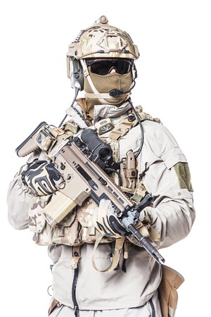 mag: Army soldier in Protective Combat Uniform holding Special Operations Forces Combat Assault Rifle. Mag recovery pouch, chest rig, military boots. Studio shot, isolated on white background