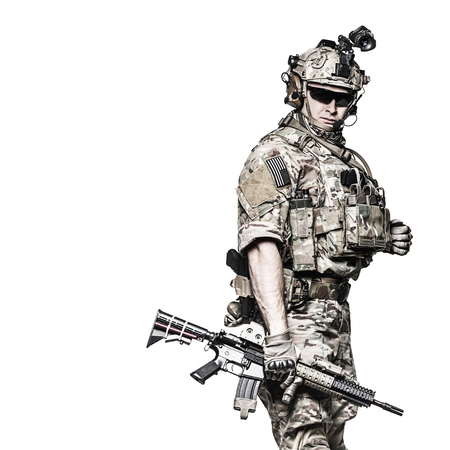his shirt sleeves: Elite member of US Army rangers in combat uniforms with his shirt sleeves rolled up, in helmet, eyewear and night vision goggles. Studio shot, white background, looking at camera, dark contrast Stock Photo