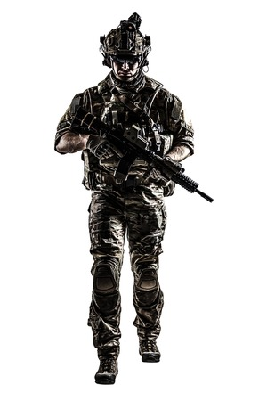treading: US Army rangers in combat uniforms with his shirt sleeves rolled up, in helmet, eyewear and night vision goggles moving walking towards camera. Studio shot, white background, dark contrast