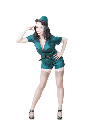 Portrait of Cute Sexy Brunette with black hair. Pin up Female Dressed in military clothing Uniform and Garrison cap saluting. Army Pin-up Girl Concept