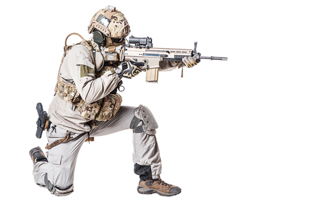 Army soldier in Protective Combat Uniform holding Special Operations Forces Combat Assault Rifle. Shooting weapon in kneeling position. Studio shot, isolated on white background Imagens - 79145740