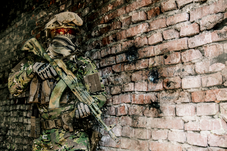 buliding: Operator of Russian special operations forces with   assault rifle and combat helmet in ruined buliding during military operation in Syria. Bullet holes on the wall Stock Photo