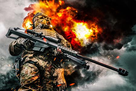 Snajper wojskowy sił specjalnych w akcji pozuje z karabinem dużego kalibru. Ciężkie wybuchy, ogień i dym kłębiący się w tle. Niski kąt widzenia