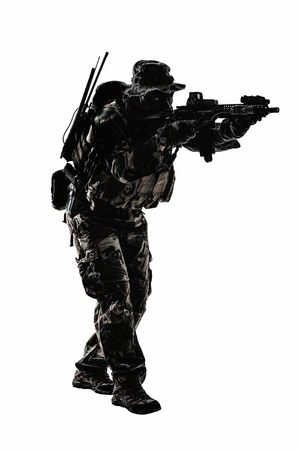 Special forces United States in Camouflage Uniforms studio shot. Holding weapons, wearing jungle hat, shooting on the move, attacking enemy. Studio shot isolated Stock Photo