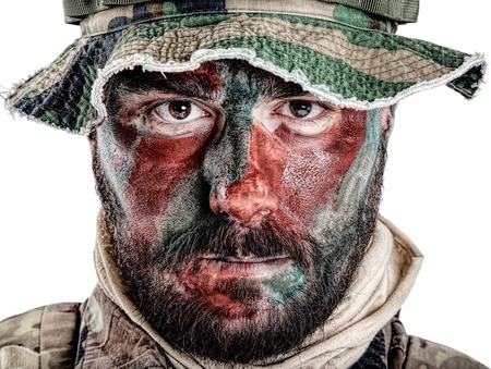 army face: Special forces United States in Camouflage Uniforms studio shot. Wearing jungle hat, Shemagh scarf, painted with red and green face. Studio shot isolated Stock Photo