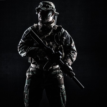he: Bearded Special forces United States in Camouflage Uniforms studio shot half length. Holding weapons, wearing jungle hat, Shemagh scarf, he is ready to kill. Contour shot, backlit Stock Photo