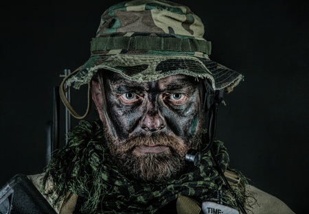 Special forces United States in Camouflage Uniforms studio shot. Wearing jungle hat, Shemagh scarf, painted face. Black background