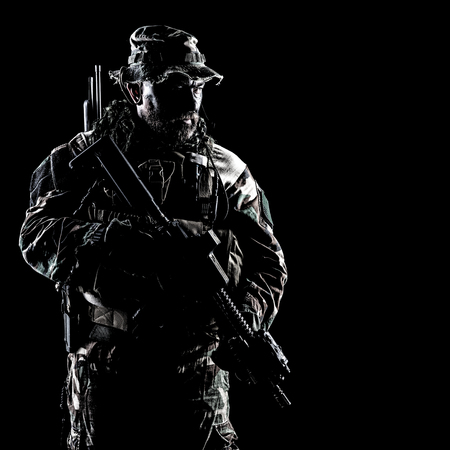 Bearded Special forces United States in Camouflage Uniforms studio shot half length. Holding weapons, wearing jungle hat, Shemagh scarf, he is ready to kill. Contour shot, backlit Stock Photo - 89549098