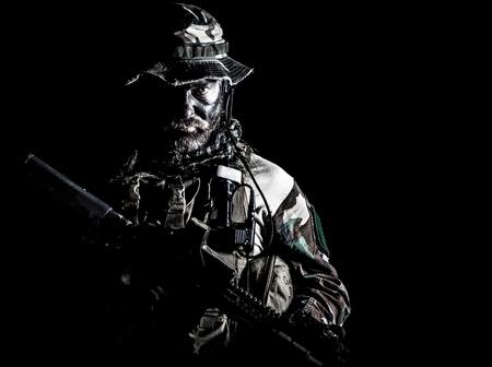 Bebaarde Special forces Verenigde Staten in Camouflage Uniformen studio shot halve lengte zwarte achtergrond. Wapens vasthouden, een junglhoed dragen, Shemagh-sjaal, hij is klaar om te doden. backlit Stockfoto