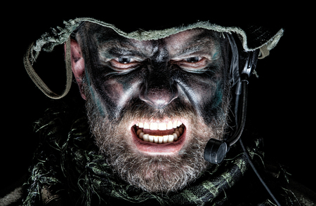 United States Commando face studio shot. Mouth opened, soldier yelling, emitting intimidate formidable frightening scream. Closeup portrait, cropped, isolated, bottom light Stock Photo