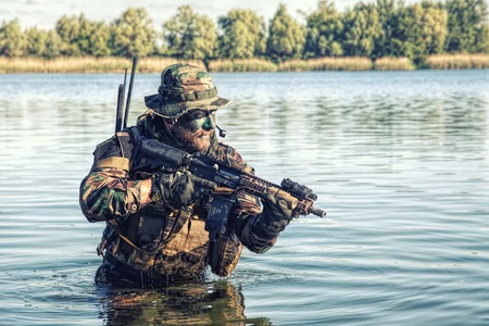Bearded soldier of special forces in action during river raid in the jungle terrain. He is waist deep in the water and mud and ready to meet enemy, survive and fight in agressive hostile environment Stock Photo