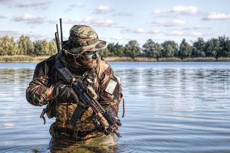 Bearded soldier of special forces in action during river raid in the jungle terrain. He is waist deep in the water and mud and ready to meet enemy, survive and fight in agressive hostile environment Imagens