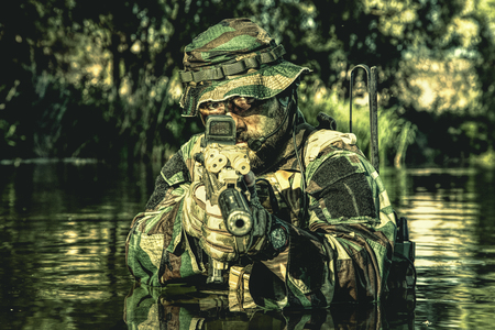 Bearded soldier in action during river raid in the jungle pointing rifle to camera. He is waist deep in the water and mud and ready to meet enemy, survive and fight in agressive hostile environment Stock Photo