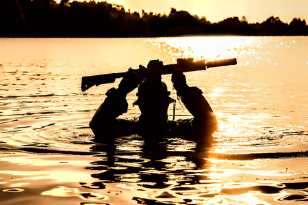 Silhouette of special forces with rifle in action during raid crossing river in the jungle waist deep in the water, with weapons over his head