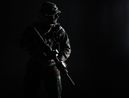Bearded Special forces United States in Camouflage Uniforms studio shot half length. Holding weapons, wearing jungle hat, Shemagh scarf, he is ready to kill. Contour shot, backlit Stok Fotoğraf