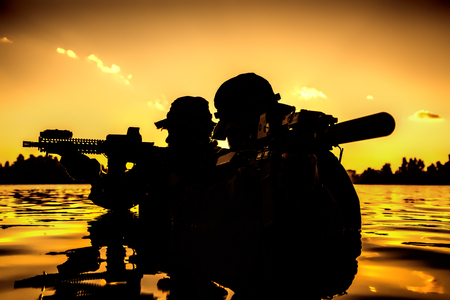 Silhouette of special forces with rifle in action during river raid in the jungle waist deep in the water. Proflie side view, half length