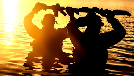 Silhouette? of special forces with rifle in action during raid crossing river in the jungle waist deep in the water