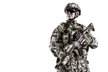 Half length low angle studio shot of special forces soldier in field uniforms with weapons, portrait isolated on white background lot of copyspace. Protective goggles glasses are on