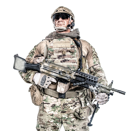 Half length low angle studio shot of big muscular soldier in field uniforms with machine gun, portrait isolated on white background lot of copyspace. Protective goggles glasses are on