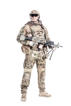 Full length low angle studio shot of big muscular soldier in field uniforms with machine gun, portrait isolated on white background lot of copyspace. Protective goggles glasses are on Stock Photo