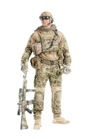 Full length low angle studio shot of big muscular soldier in field uniforms with sniper rifle, portrait isolated on white background lot of copyspace. Protective goggles glasses are on