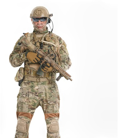 Half length low angle studio shot of special forces soldier in field uniforms with weapons, portrait isolated on white background, front view. Protective goggles glasses are on