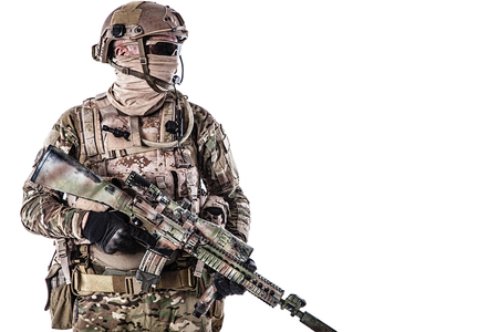 Half-length low angle studio shot of special forces soldier in field uniforms with weapons, portrait isolated on white. Protective goggles glasses are on Stock Photo