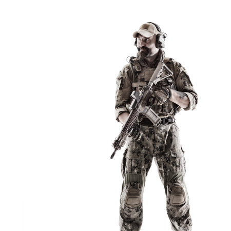 Half length low angle studio shot of special forces soldier in field uniforms with weapons on his shoulder, portrait isolated on white background
