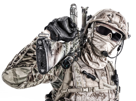 Half length low angle studio shot of special forces soldier in field uniforms and face mask with sniper rifle on his shoulder, portrait isolated on white background Imagens