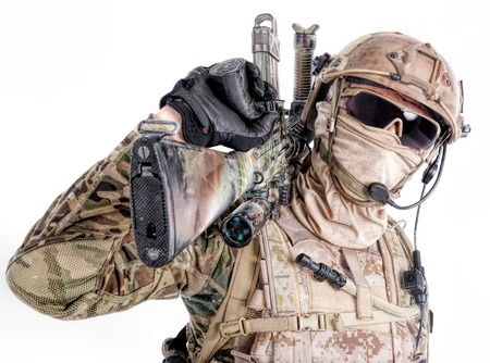Half length low angle studio shot of special forces soldier in field uniforms and face mask with sniper rifle on his shoulder, portrait isolated on white background Stock Photo