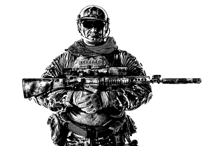 Half length cropped studio shot of big muscular soldier in field uniforms with sniper rifle, portrait isolated on white background lot of copyspace. Protective goggles glasses are on
