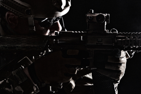 Studio contour backlight shot of special forces soldier in uniforms pointing weapons, closeup portrait on black background