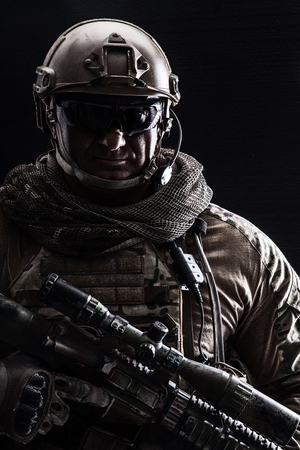 Studio contour backlight shot of special forces soldier in uniforms with weapons, portrait on black background Stock Photo