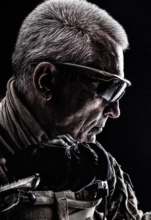 Close up studio shot of special forces white-haired veteran with a knife. Sudden death concept