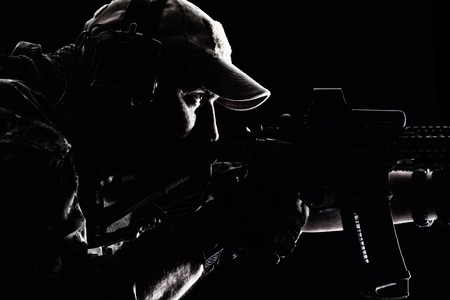 Studio contour backlight shot of special forces soldier in uniforms and baseball cap, pointing rifle, closeup portrait on black background