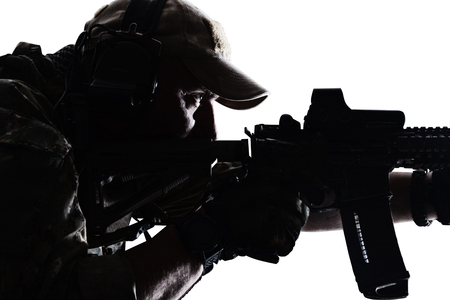 Studio contour backlight shot of sportsman in baseball cap, pointing rifle, closeup portrait on white background