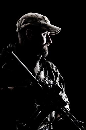 Half lengte studio contour achtergrondverlichting shot van bebaarde speciale troepen soldaat in uniformen met wapens, portret op zwarte achtergrond.