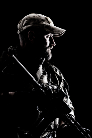 Half length studio contour backlight shot of bearded special forces soldier in uniforms with weapons, portrait on black background.