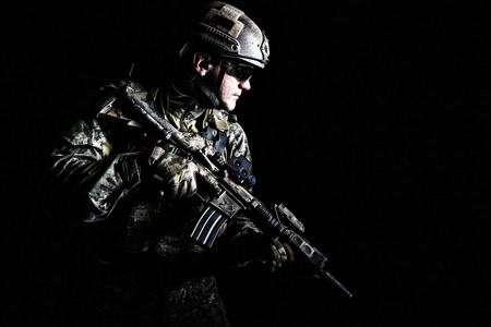 gunfire: Half length low angle studio shot of special forces soldier in field uniforms with weapons, portrait on black background. Protective goggles glasses are on