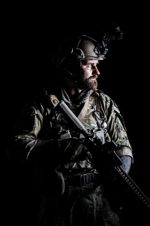 Studio contour backlight shot of special forces soldier in uniforms with weapons, portrait on black background Reklamní fotografie - 87703883