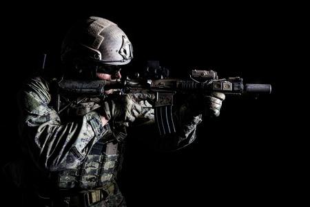 Halve lengte lage die hoekstudio van speciale krachtenmilitair wordt geschoten in gebiedsuniformen met wapens, portret op zwarte achtergrond. De veiligheidsbrilbril is ingeschakeld Stockfoto