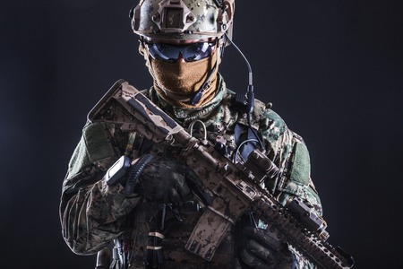 Half length studio shot of special forces soldier in field uniforms with weapons, portrait on black background. Protective goggles glasses are on